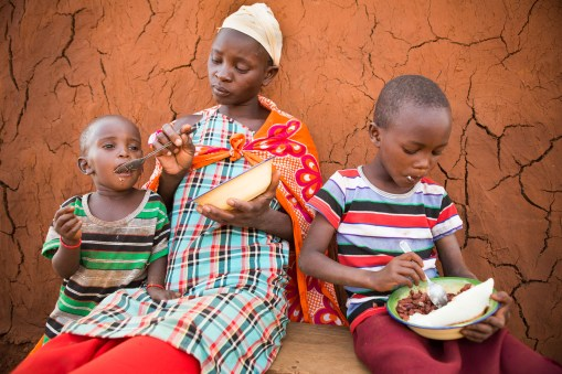 A family share a meal of beans and cornmeal porridge Emali district, Kenya.