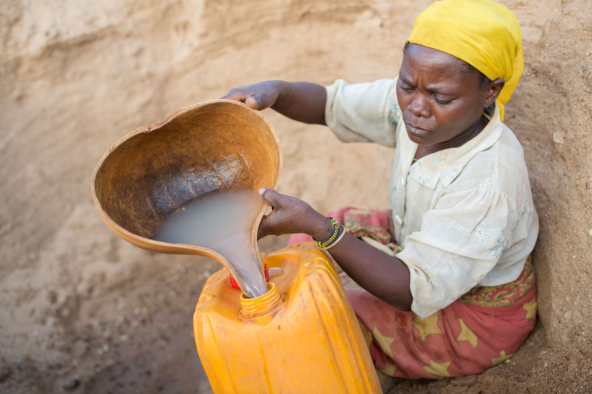 A woman fetches water from a river bed in Makueni County, Kenya.