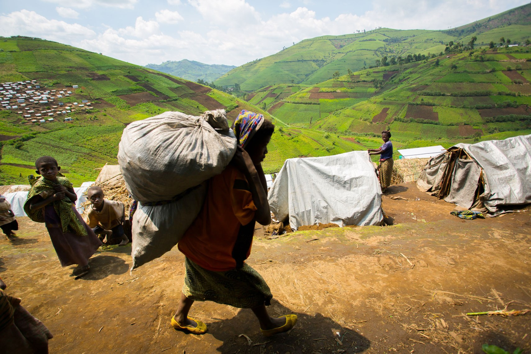 A woman totes her belongings through a hillside refugee camp in North Kivu Province, DRC.