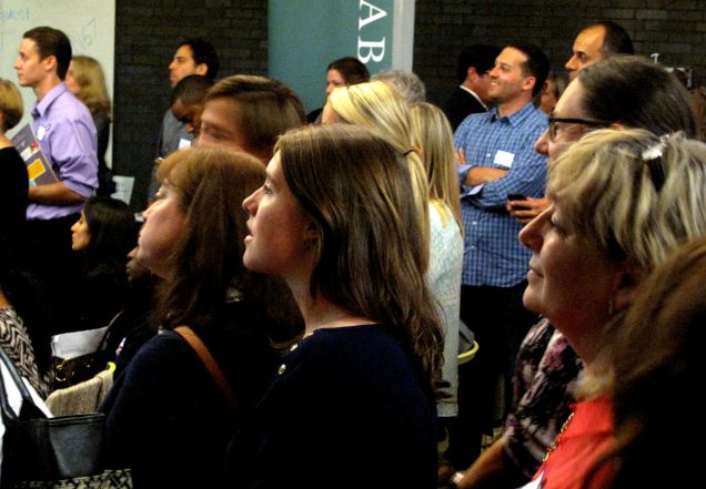 After having a chance to network, the crowd gathers to hear presentations from each of the companies.