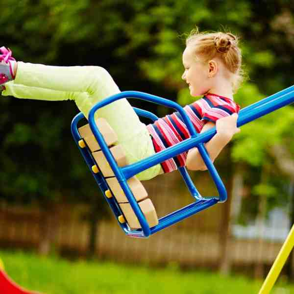 Happy little girl on a swing set