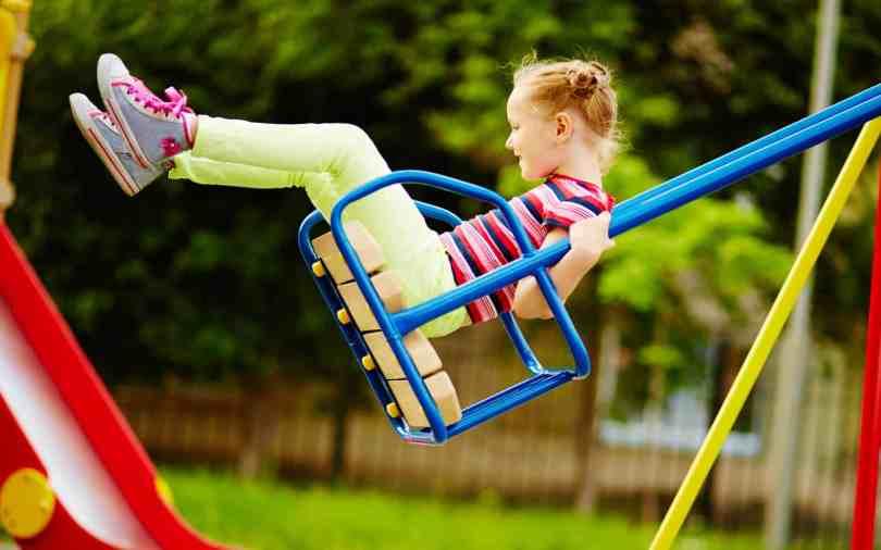 Happy little girl on a swing set