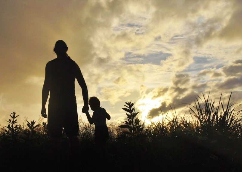 Man walking with child in a field for the article V