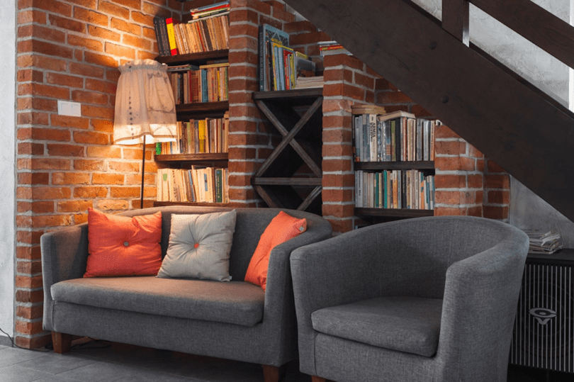 grey compact sofas in front of bookcase in cosy living room