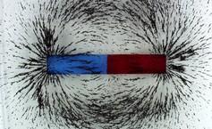 Opiłki żelaza i magnes odwzorujące pole magnetyczne Ziemi