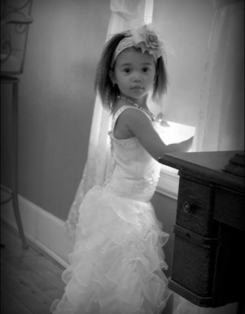 This charming young flower girl looks gorgeous in her dress.