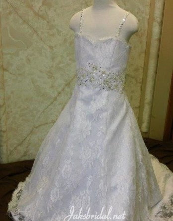 White lace flower girl dress with train. A line sweetheart gown with silver and pearl beaded shoulder straps and belt.