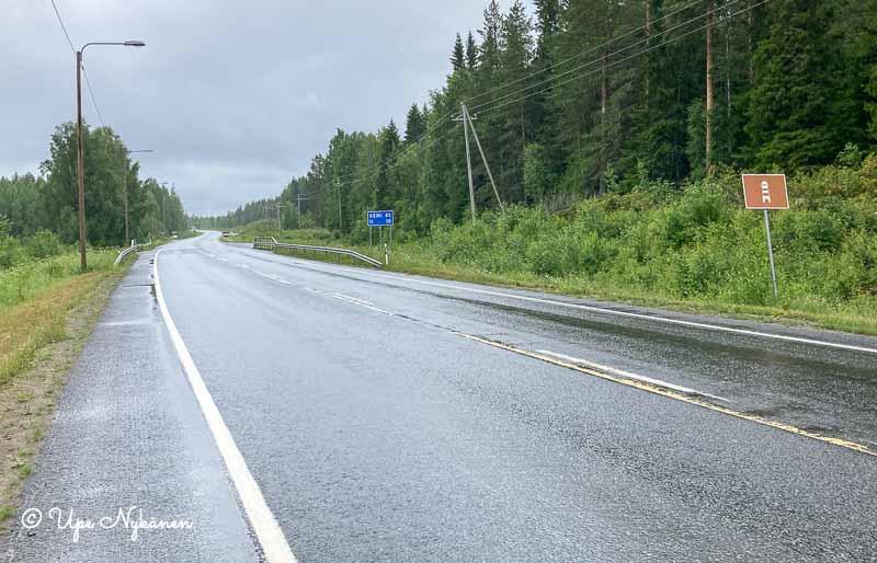 Sateen kastelema Haukiputaantie, jonka varressa Maisematie-liikennemerkki.