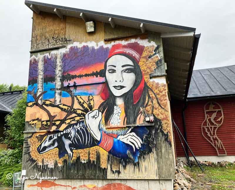Saamelaisasuun pukeutunutta naista ja luurankoporoa esittävä seinämaalaus Kulttuurikauppilan ulkoseinässä, Ii.