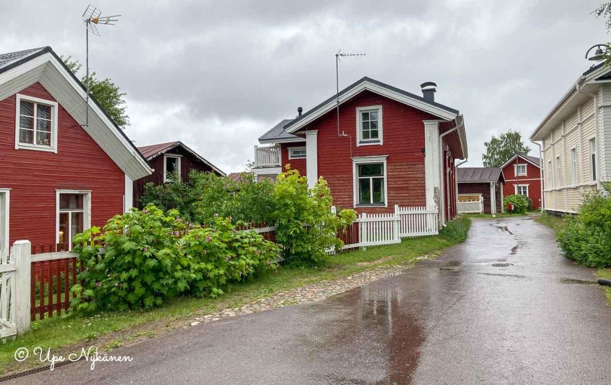 Iin wanhan haminan kapea katu, jonka varressa punaisia ja vaaleita vanhoja omakotitaloja.