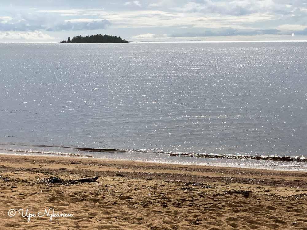 Hiekkaranta ja sen takana tyyni, kimmeltävä Perämeri sekä saari.