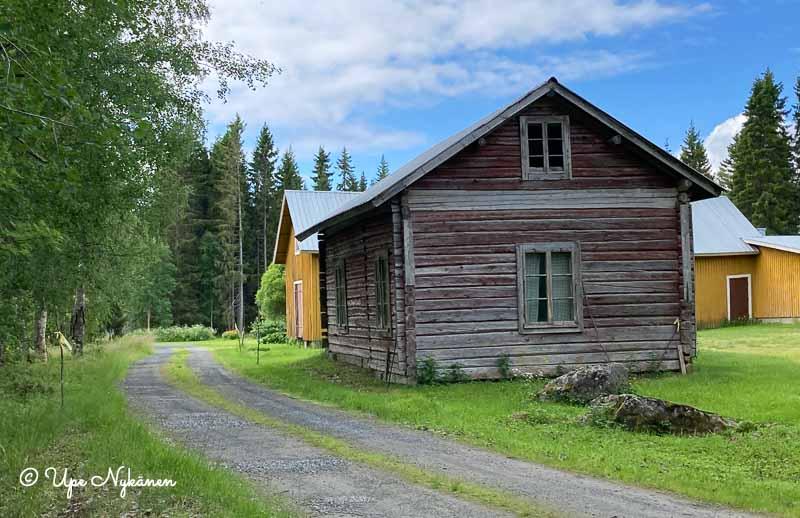Kapea tie kulkee vanhan maalaistalon pihapiirin vieritse, vanha hirsitalo ihan tien vieressä.