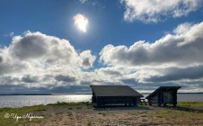 Laavu ja puuvaja Simoniemen satamassa Perämeren rannalla, isot pilvet taivaalla ja aurinko paistaa.