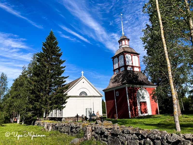 Simoniemen vanha valkoinen kirkko, punainen kellotapuli ja kirkkomaa, jota kiertää kiviaita.