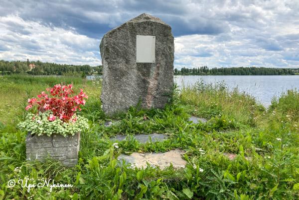Kivinen muistomerkki Kemijoen rannassa, vieressä kukkaistutukset. Jääkärieverstiluutnantti Mannerheim-ristin ritari Auno Kuirin synnyinkodin paikka.