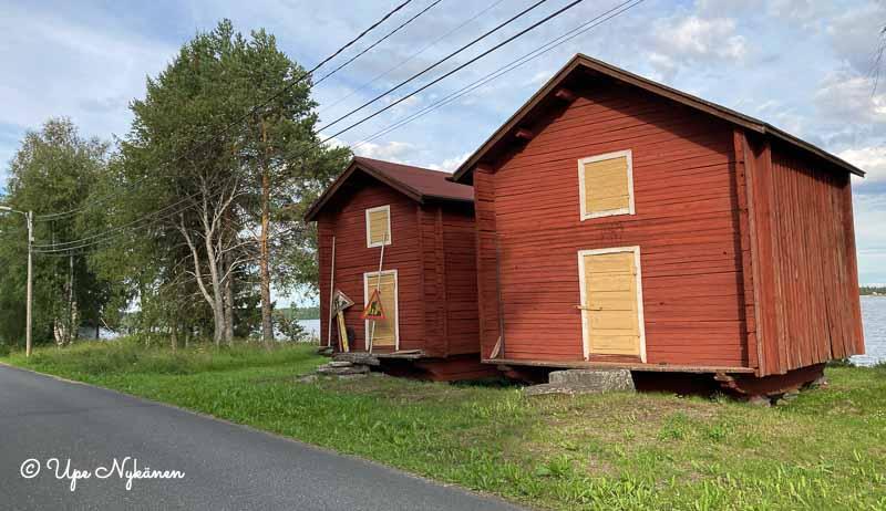 Kaksi punaista rantamakasiinia Kemijoen rannassa, keltaiset ovet.