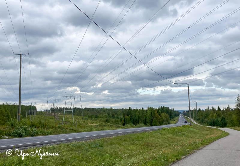 Suurjännitelinjat risteävät nelostien ja kävelytien yli, pilvinen taivas.