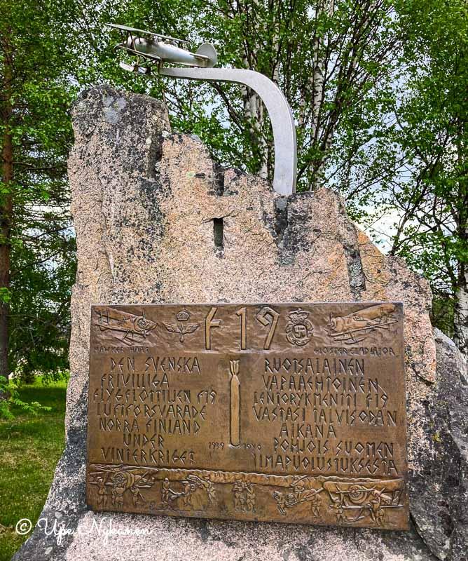 Kivinen muistomerkki, jonka yläpuolella pieni metallinen lentokone ja kivessä F19-lentorykmentin muistolaatta.