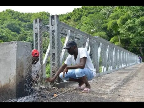 Kenyon Hemans/Photographer Garfield Edward (partially hidden) and Withman Hunt fasten a  fence along the sides of  the newly built Chesterfield Bridge in St Mary.