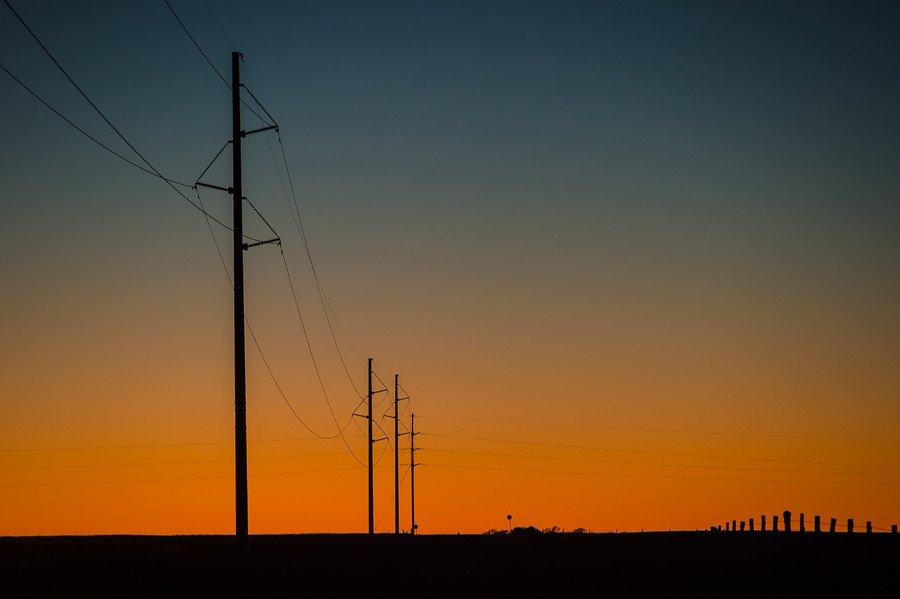 The sun sets behind electrical utility lines in the Oklahoma panhandle. Tri-County Electric Coop TCEC