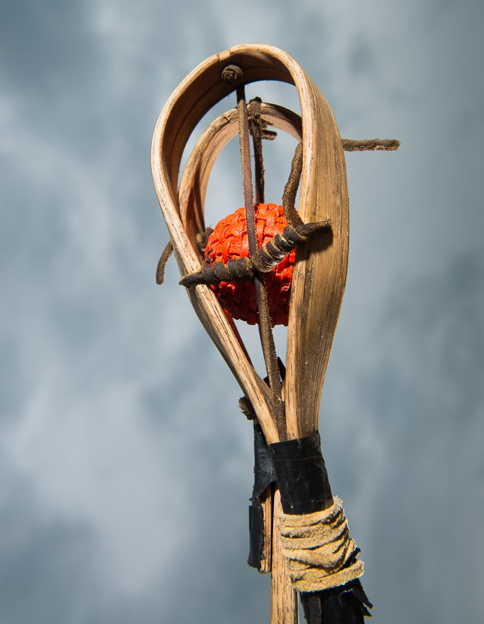 The ball is made out of wrapped leather and the sticks are hand made from hickory wood and leather.