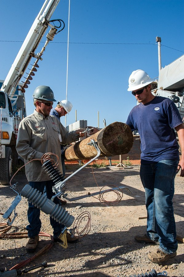 The lineman crew prepare an electrical pole for installation at a job site in western Oklahoma.
