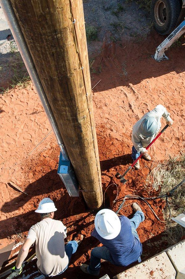 Northfork Electric Coop lineman filling in dirt around an electrical utility pole in Elk City, Oklahoma.