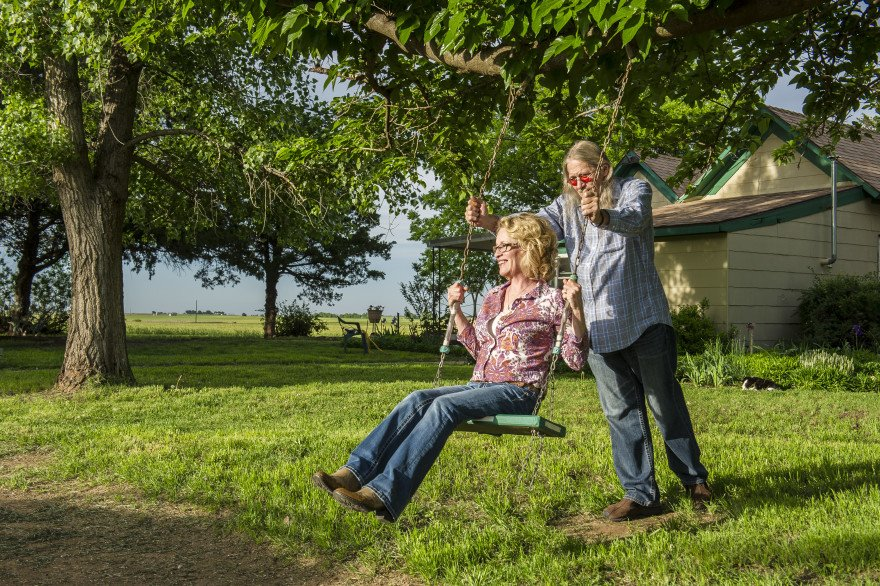 Perry and Jennifer Plett on the swing behind their house. Their children played on the swing and now grandchilder come to swing from the tall Mulberry trees surrounding the Plett homestead.