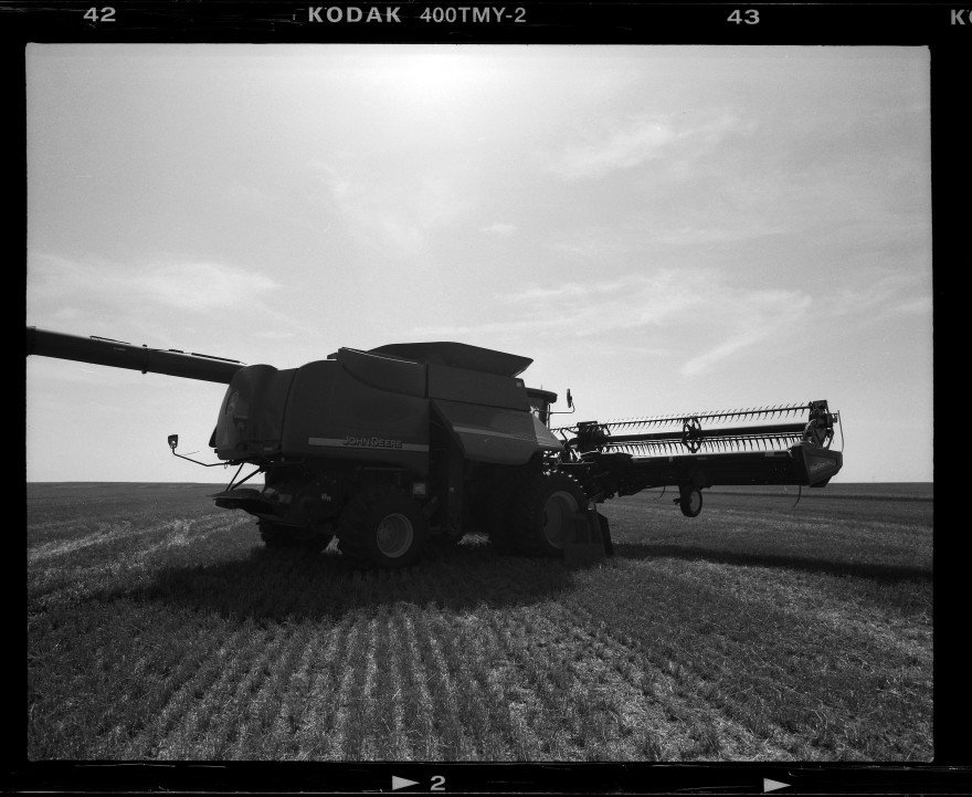 John Deere combine undergoing routine morning maintenance on a wheat field in northern Oklahoma during the 2015 wheat harvest. Shot with Pentax 67 using Kodak TMAX-400 film.