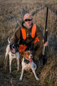 Cory Stokes poses with his dog Annie and another one of his dogs while pheasant hunting in South Dakota.