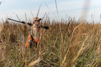 Cory Stokes walks through head-high cattail marsh as he hunts for pheasants in South Dakota.