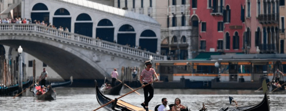 A gondolier with tourists on the Canal Grande CBC News | James Alexander Michie