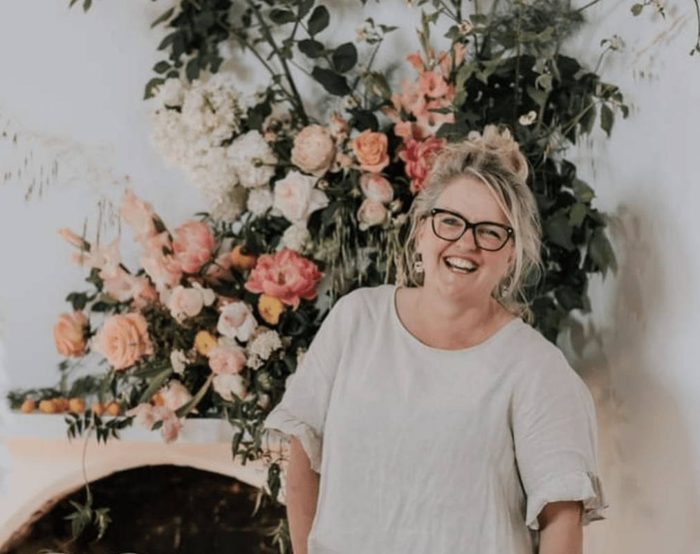 Photo of Georgie James behind a floral background