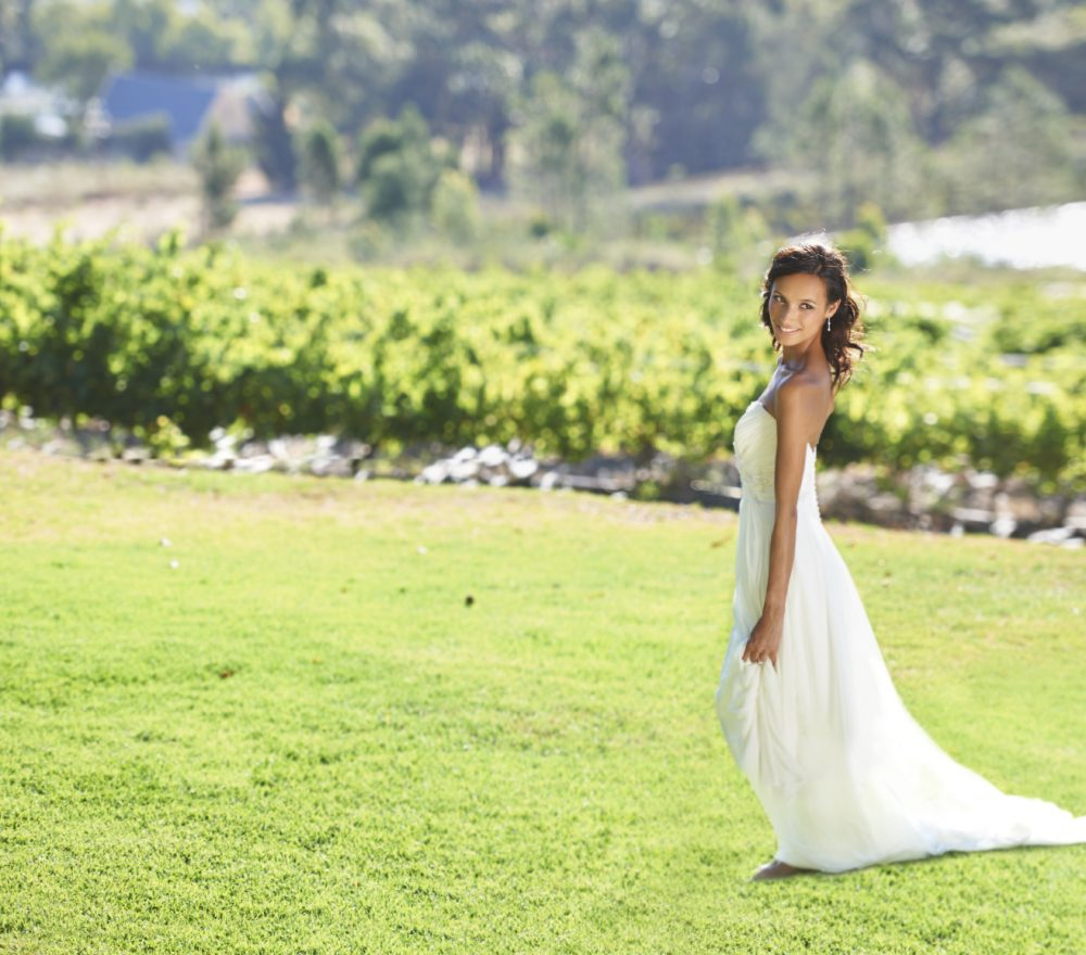 A beautiful bride standing in front of a vineyard