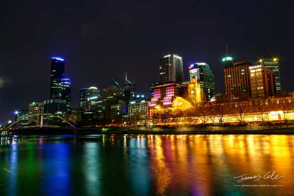 Colourful waterfront of Melbourne City and Flinders street station historic building with lights reflecting off the water
