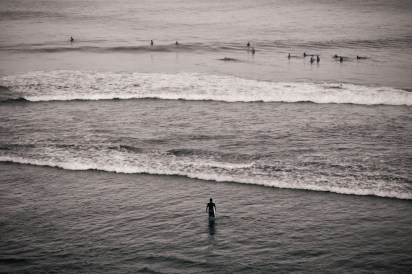 A lone surfer stands on the reef.