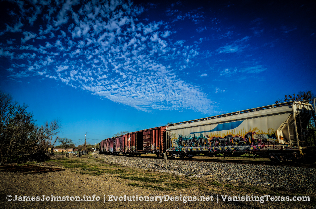 Kansas City Southern Evening Train passing Through Greenville, Texas - Gotta love all the graffiti on the side cars.