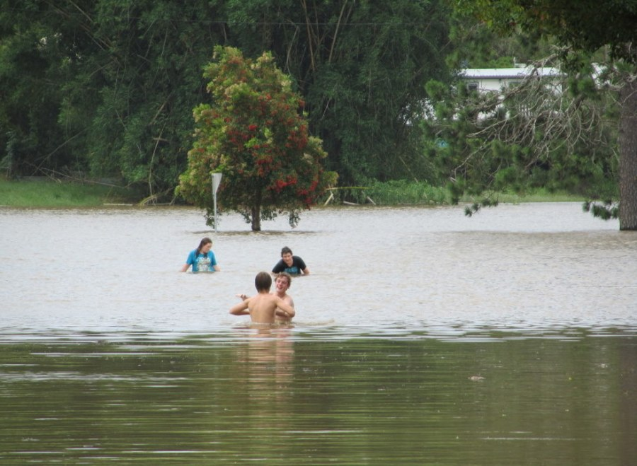 Kids swimming in flood water at North Lismore. Not clever kids.