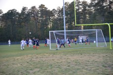 The offensive players kept the ball near the goal and set up to take a shot.