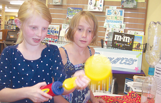 Courtesy photo. Kaylee Fiedler, left, and Lillian Brooks blow up a balloon as the first step in creating a hovercraft in the Mad Scientist Lib-Lab available Tuesday through Saturday through Aug. 30 at Prendergast Library, 509 Cherry St., Jamestown. Kits for the Family Experi-Event tied to this year's Summer Reading theme were provided by the Chautauqua-Cattaraugus Library System. For information, call 484-7135.