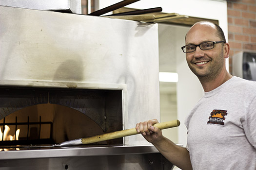 Andrew Anderson stands by the brick oven where they cook the pizzas at the Brick City Market and Deli