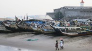 Watch boats docked on the beach and fisherman tending their nets