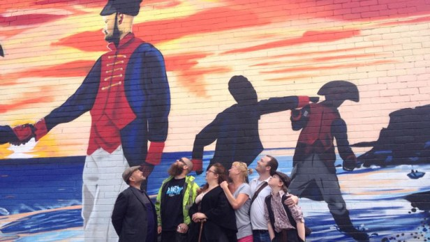 Rob Reed, Frank Styles, Corinne Kilvington, Jane Nesbitt, James Whitman, and George Cooperwaite, in front of a mural depicting 'The Battle of Hendon'.
