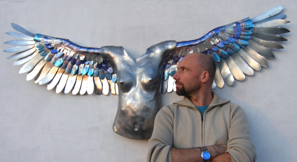 Winged female torso sculpture in aluminium and Red Bull cans with the artist Jamie McCartney
