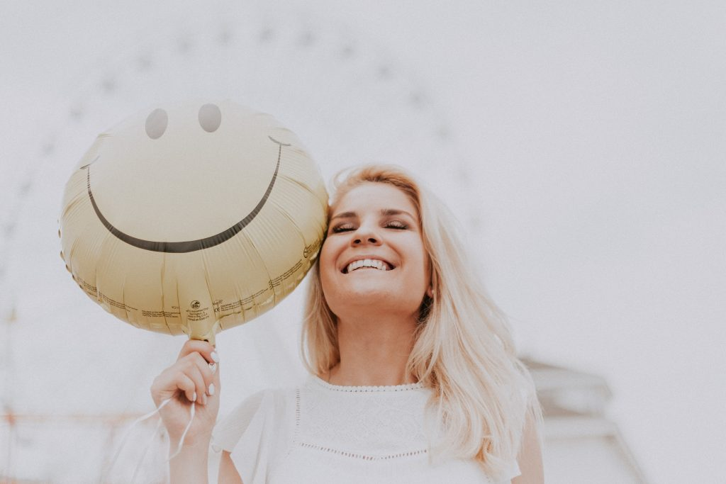 a blonde woman stood with a balloon that has a yellow smiley face, symbolising success and fulfilment