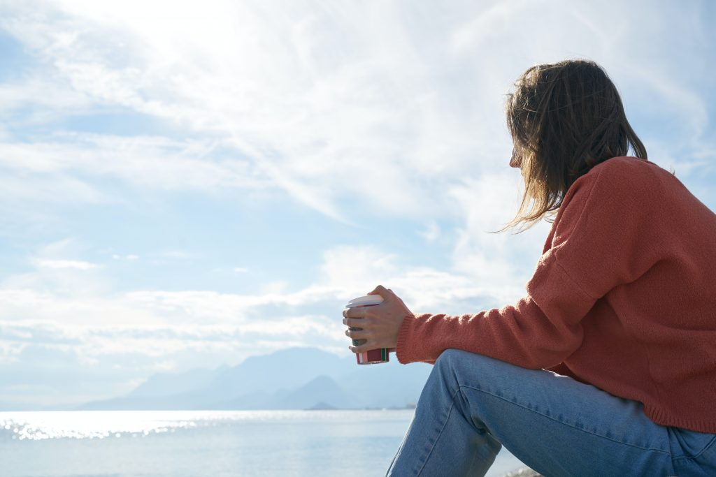 woman holding coffee looking out onto the horizon, symbolising thinking