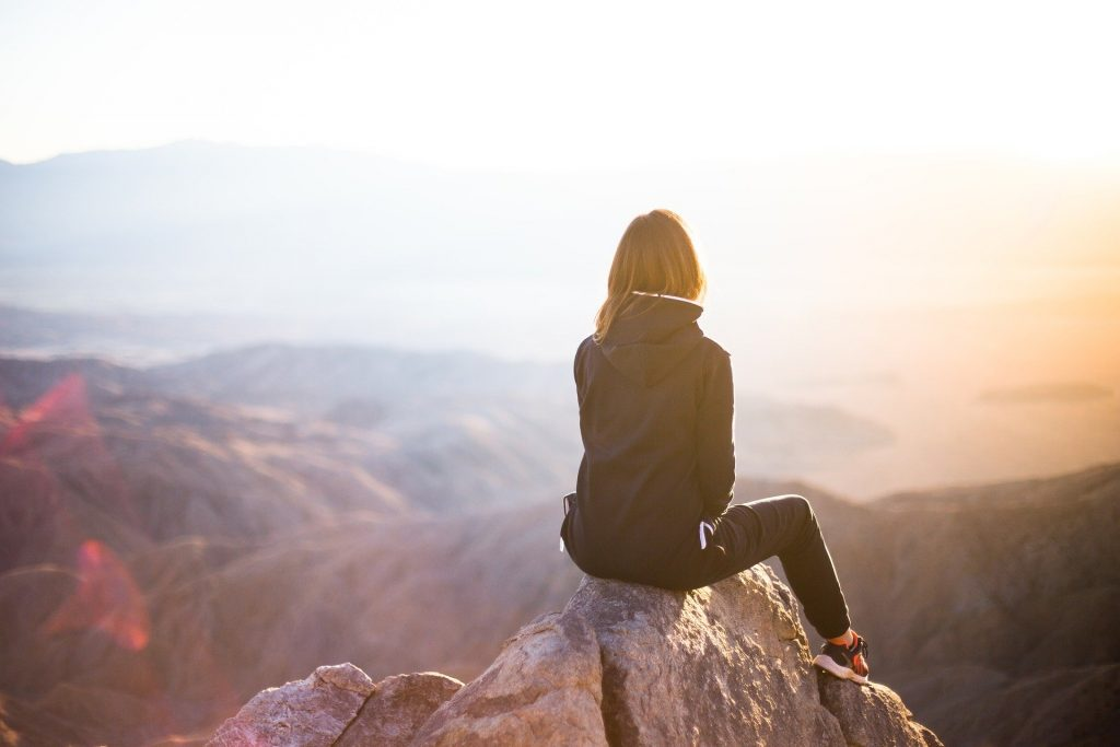 a picture of a woman sitting at the edge of a rock looking down into a valley. Symbolising having reached the guiding nature of her goals.