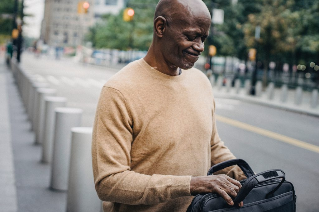 image of a man walking in the street looking into his bag, realising he has forgotten something - showing the value of a to do list in not forgetting things in business