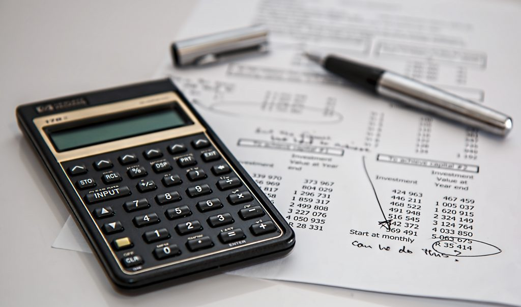 picture of calculator, papers and pen. signifying accounts. most entrepreneurs will have to bookkeep in the beginning