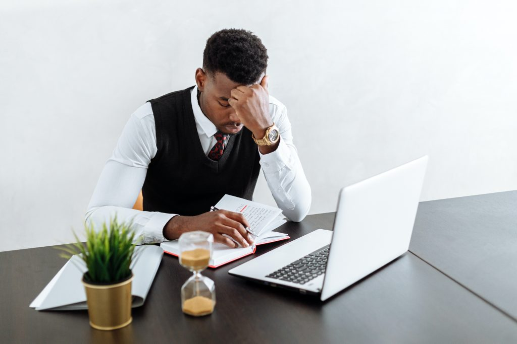 man sitting at his desk on his laptop looking stressed - in business